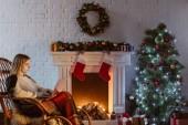 mladá žena na přenosném počítači v obývacím pokoji zdobené vánoční proutěné houpací křeslo