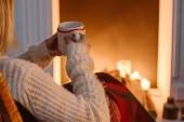 abgeschnittene Ansicht einer Frau in karierter Decke, die eine Tasse Kaffee zu Hause hält
