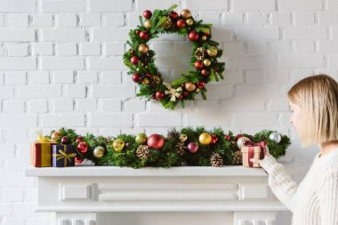christmas wreath and decorations over fireplace mantel with white brick wall