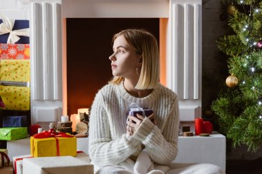 young woman sitting, holding present and looking away at fireplace