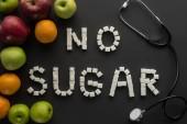 pohled shora bez cukru fráze z kostek cukru s stetoskop a ovoce na černém pozadí