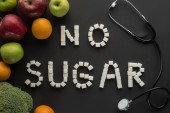 no sugar lettering made of cubes among fruits and vegetable on black