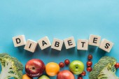 diabetes lettering made of wooden cubes, vegetables and fruits with copy space on blue background