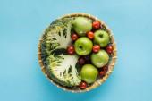 pohled shora zeleniny a jablka v proutěná ošatka na modrém pozadí