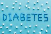 Fotografie cukrovkaslovo z jednorázových jehel se kostky cukru na modrém pozadí