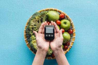 top view of glucometer in female hands with vegetables and apples on blue background
