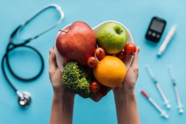 fruits and vegetables in female hands with medical equipment on blue background
