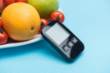 close up view of glucometer with tomatoes and fruits on blue background