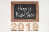 Draufsicht des Textes Frohes neues Jahr auf Kreidetafel mit Datum 2019 aus Sperrholz isoliert auf weiß