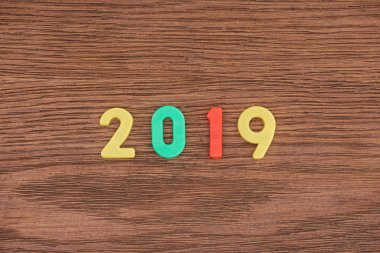 Top view of 2019 date made of colorful numbers on wooden background stock vector