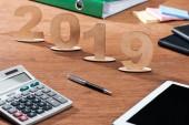 2019 datum vyrobené z dřevěných čísel Kalkulačka a šablon na kancelářský stůl