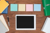 Photo top view of four sticky notes and digital tablet with blank screen on wooden office desk