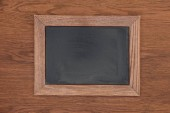 top view of empty chalk board on wooden background