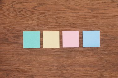 Top view of four sticky notes on wooden tabletop stock vector