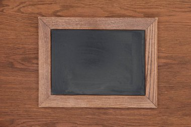 Top view of empty chalk board on wooden background stock vector