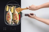 oříznutý snímek osoby vaření chutné ryby s rozmarýnem a cherry rajčátky na elektrický sporák