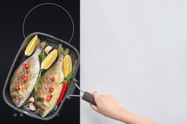 cropped shot of person cooking tasty fried fish with lemon, rosemary and cherry tomatoes
