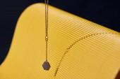 Krásné luxusní náhrdelník na žluté a černé pruhované povrchu