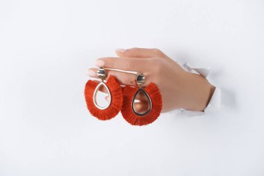 cropped image of woman holding hand with beautiful luxury red earrings through white paper