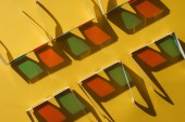 Fotografie top view of cardboard 3d glasses in two rows with shadows on yellow background