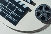top view of clapperboard and film reel with cinema tape on grey background
