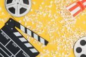 film orsók, clapperboard és felborult csíkos vödör a pattogatott kukorica, elszigetelt, a sárga