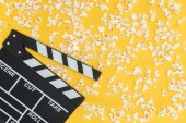 top view of clapperboard and fresh tasty popcorn isolated on yellow