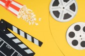 top view of clapperboard, overturned striped bucket with popcorn and film reels with cinema tape isolated on yellow