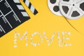 clapperboard, film reels and movie lettering made with popcorn isolated on yellow