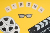 wooden cubes with cinema lettering, clapperboard, film reels and stereoscopic 3d glasses isolated on yellow