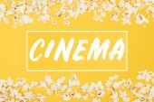 Fotografie cinema lettering in horizontal frame made of fresh popcorn isolated on yellow