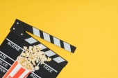 Fotografie cinema clapperboard and overturned bucket with popcorn isolated on yellow