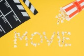 clapperboard, overturned striped bucket and movie lettering made with popcorn isolated on yellow