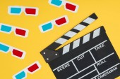 plastic 3d glasses and clapperboard isolated on yellow