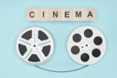 dřevěné kostky s cinema nápisy a film navijáky kino páskou mezi nimi izolované na modré