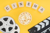 Fotografie top view of wooden cubes with cinema lettering, clapperboard, film reels and popcorn bucket isolated on yellow