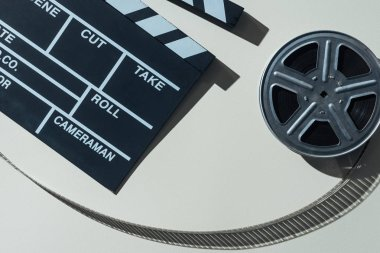 Top view of clapperboard and film reel with cinema tape on grey background stock vector