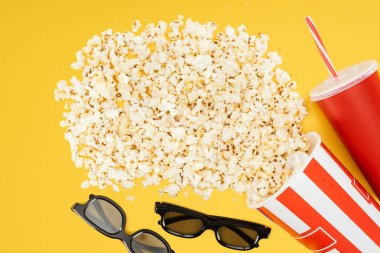 top view of 3d glasses, red disposable cup with straw and overturned striped bucket with popcorn isolated on yellow