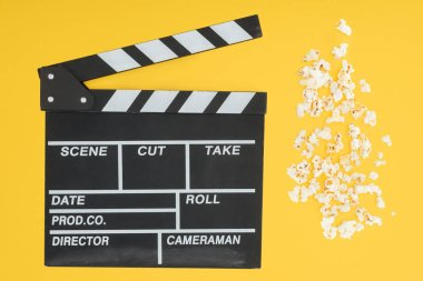 top view of clapperboard and fresh crunchy popcorn isolated on yellow