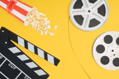 Top view of clapperboard, overturned striped bucket with popcorn and film reels with cinema tape isolated on yellow stock vector