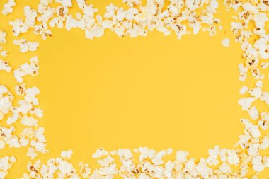 frame made of fresh tasty popcorn isolated on yellow
