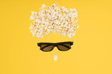 stereoscopic 3d glasses and tasty popcorn isolated on yellow