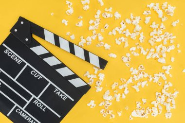 Top view of cinema clapperboard and crunchy popcorn isolated on yellow stock vector