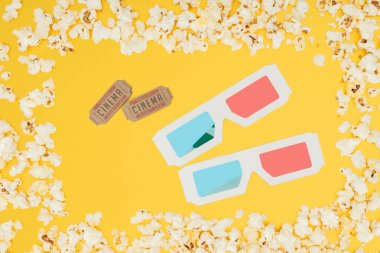 Cinema tickets and 3d glasses in frame made of tasty popcorn isolated on yellow stock vector