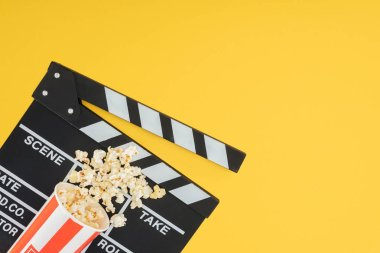 cinema clapperboard and overturned bucket with popcorn isolated on yellow