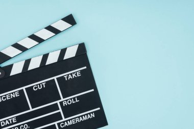 opened black movie clapperboard isolated on blue
