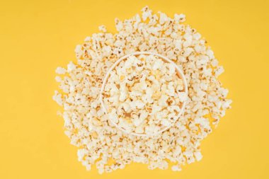 Top view of carton bucket and scattered popcorn isolated on yellow stock vector