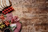 pohled shora na krájecí desky s chutné salám, uzené klobásy, olivy, rajčata a chleba na dřevěný stůl s rozptýlenými pepře