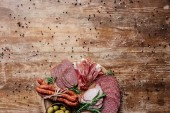 Fotografia top view of cutting board with olives and sliced salami, prosciutto and ham on wooden table with scattered spices