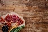 pohled shora na kulaté prkénko s chutné parmská šunka, salám, uzené klobásy, olivami a bylinkami na dřevěný vintage stůl s rozptýlenými koření